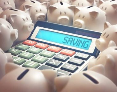 """Calculator amid several piggy banks showing on the display the word """"SAVING"""". 3D illustration, business and finance concept."""