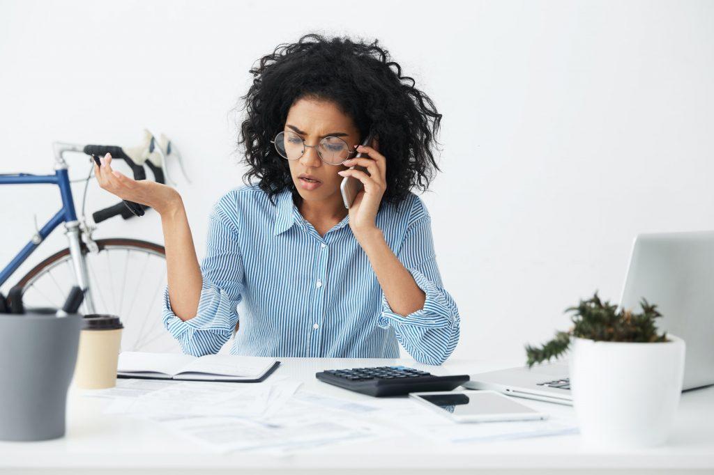 Businesspeople, modern technology and communication. Upset mixed race businesswoman having stressful