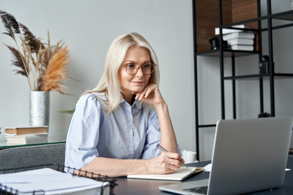 Middle aged woman watching professional training class online virtual meeting.