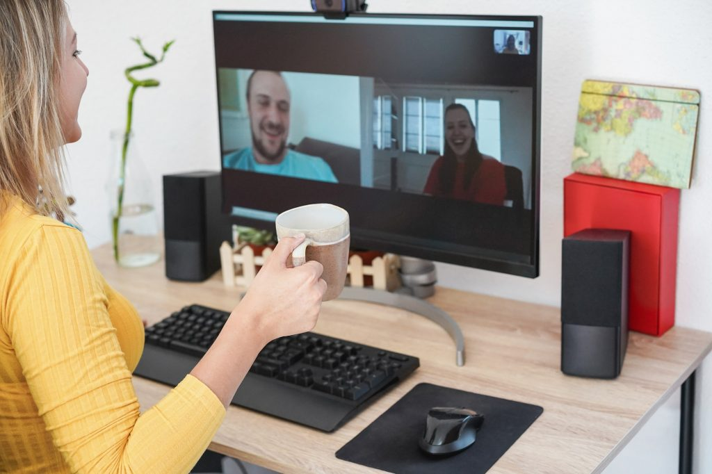 Young woman having an online video call with friends while drinking coffee at home - Focus on cup